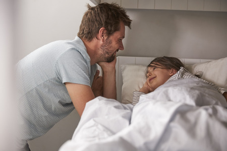 Father Saying Goodnight To Daughter At Bedtime Stock Photo