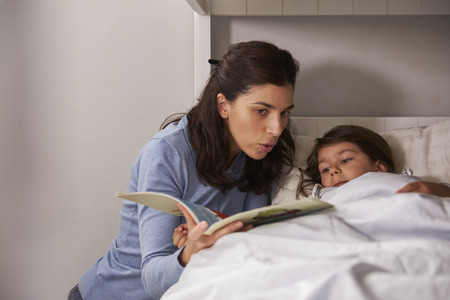 Mother Reading Story To Son At Bedtime