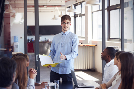 addressing: Young man holding document addressing colleagues at meeting Stock Photo