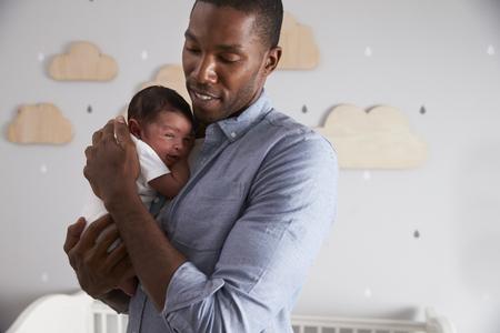 Father Holding Newborn Baby Son In Nursery