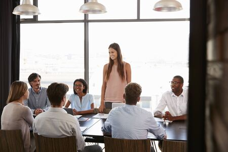 Young woman standing at a meeting in a business boardroom