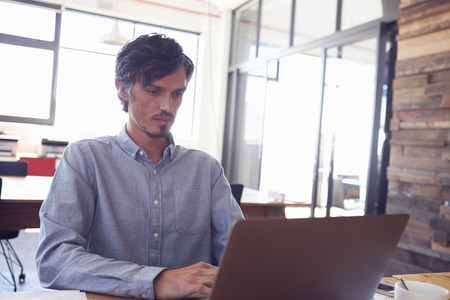 Mid-adult white man working in an office using laptop, close up Фото со стока - 79572052