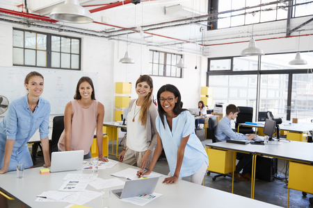 Female business team stand at office desk looking to camera