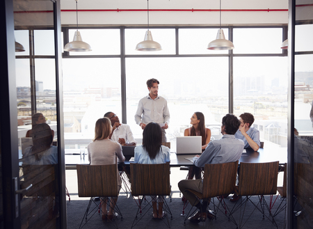 Young man stands addressing team at a meeting in a boardroom Stock Photo