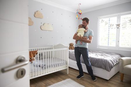 Father Comforting Newborn Baby Son In Nursery
