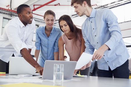 Four young business colleagues stand around laptop in office Stock Photo
