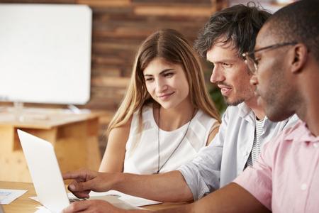 Trois collègues travaillent ensemble à l'ordinateur portable, de près