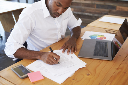Elevated view of young black man working at office desk