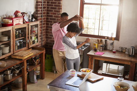 Mixed race couple dancing in kitchen, elevated view