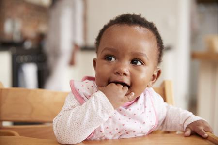 Mignonne petite fille portant un bavoir assis sur une chaise haute Banque d'images - 79572492