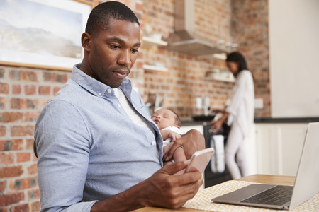Father On Laptop Holds Newborn Son As Mother Makes Meal