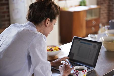 어깨 식으로 뷰를 통해 아침에 노트북을 사용하는 젊은 여성