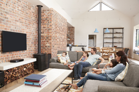 Family Sit On Sofa In Open Plan Lounge Watching Television Stockfoto