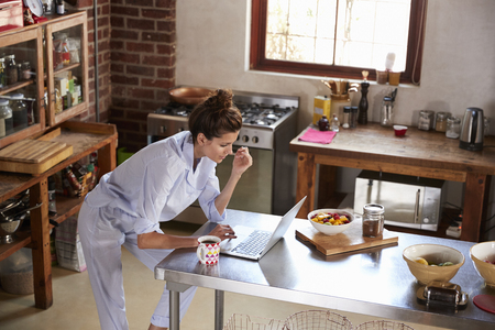 Young woman in pyjamas using laptop at breakfast, high angle