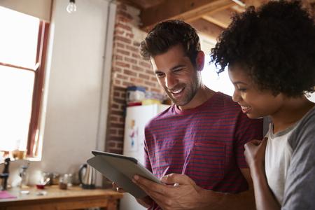 부엌에서 태블릿을 사용하여 젊은 혼합 된 인종 커플을 닫습니다.