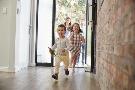 Bambini eccitati che corrono casa con i genitori Archivio Fotografico - 79573179