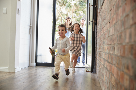 Opgewekte kinderen die thuis met ouders aankomen Stockfoto