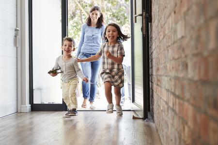 Bambini eccitati che corrono casa con i genitori Archivio Fotografico - 79573301