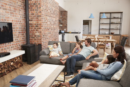 Family Sit On Sofa In Open Plan Lounge Watching Television Stock Photo
