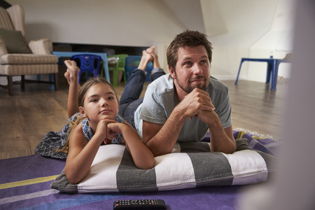 Father And Daughter Watching Television In Playroom Together Reklamní fotografie