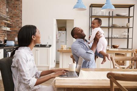 어머니는 아버지가 아기 딸을 붙잡기 때문에 집에서 일합니다. 스톡 콘텐츠