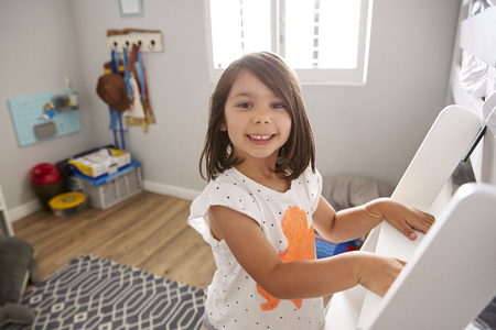 Portrait Of Girl Climbing Ladder To Bunk Bed Stock Photo