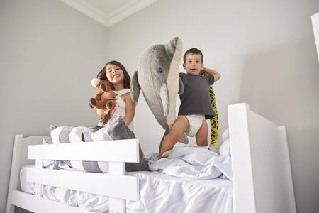 Portret van kinderen die met speelgoed in stapelbed spelen