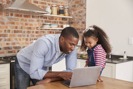 Father And Daughter Using Laptop In Kitchen At Home