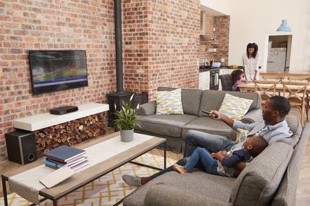 Padre e hijo se sientan en el sofá en el salón viendo televisión