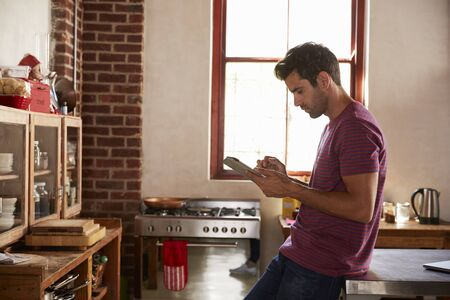 Young man using tablet computer in kitchen, waist up Stock Photo