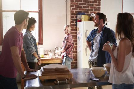 Five friends talk standing in kitchen, close up