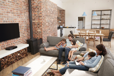 Family Sit On Sofa In Open Plan Lounge Using Technology
