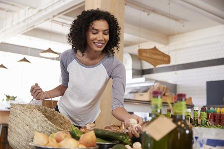 Woman Shopping For Organic Produce In Delicatessen Фото со стока