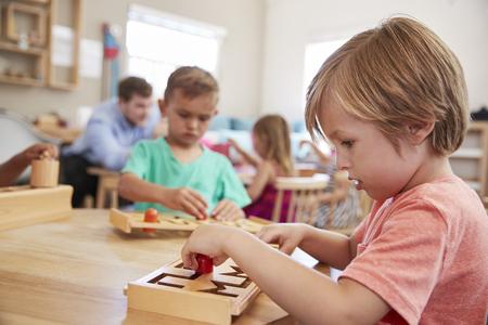 Alumna trabajando en la mesa en la escuela Montessori Foto de archivo - 79573642