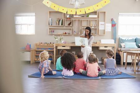 Leraar In Montessori School Lezing Aan Kinderen Op Verhaal Tijd Stockfoto - 79573686