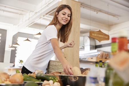 デリカテッセンで有機農産物のショッピング女性