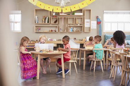Wide Angle Shot Of Pupils Working At Tables In Montessori School