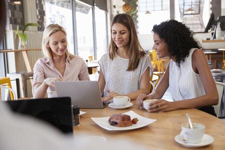 Three Businesswomen Having Meeting In Coffee Shop Imagens