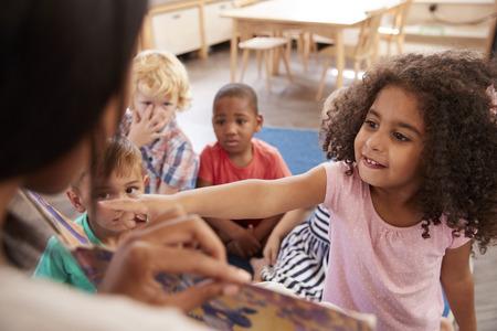 Lèves à l'école Montessori regardant livre avec professeur Banque d'images - 79574096