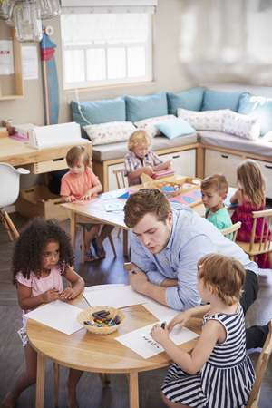 Teacher And Pupils Practicing Writing In Montessori School Stock Photo