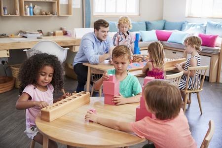 Leraar en leerlingen werken aan tafels in Montessori School
