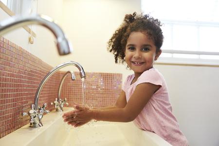 몬테소리 학교에서 여성 학생은 화장실에서 손을 씻고 스톡 콘텐츠