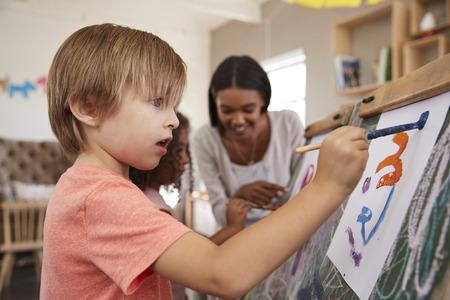 美術の授業で子どもたちを助けるモンテッソーリ学校の先生