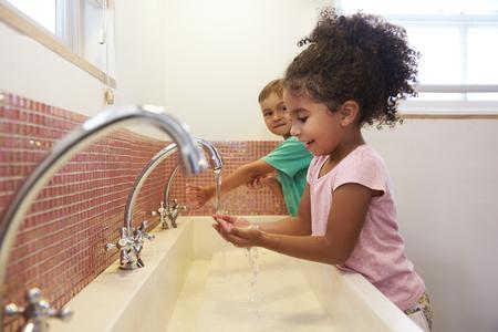 Montessori School의 학생들은 화장실에서 손을 씻는다.
