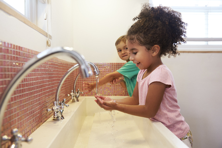 Pupils At Montessori School Washing Hands In Washroom Zdjęcie Seryjne