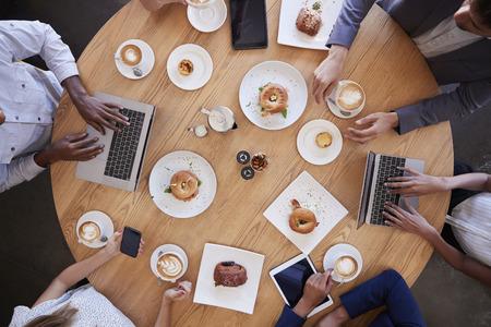 コーヒー ショップで実業家の会議のオーバー ヘッド ショット