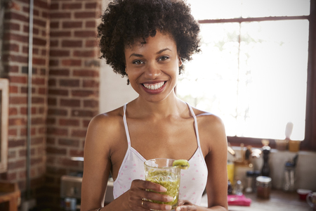 Happy mixed race woman holding smoothie, looking to camera