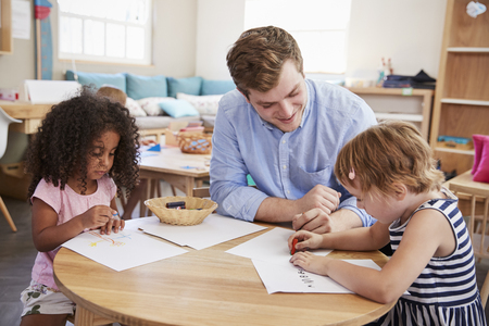 Teacher And Pupils Practicing Writing In Montessori School Stock Photo