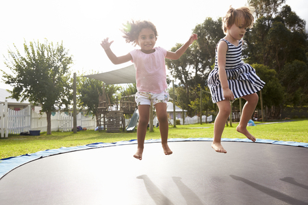 Children At Montessori School Having Fun On Outdoor Trampoline Zdjęcie Seryjne