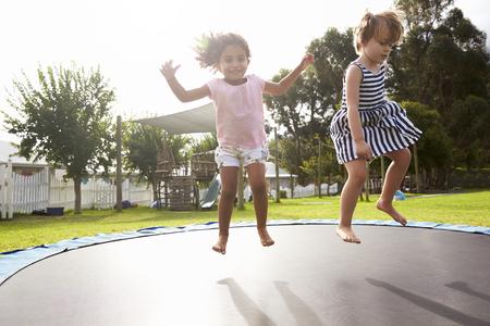 Niños en la escuela Montessori divirtiéndose en trampolín al aire libre Foto de archivo - 79574337